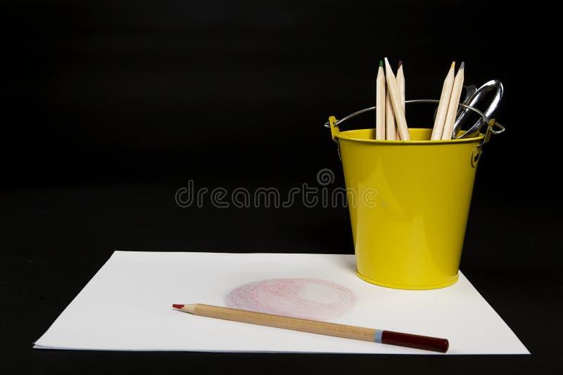 Gelber Eimer farbige Bleistifte mit einer Zeichnung stockbilder