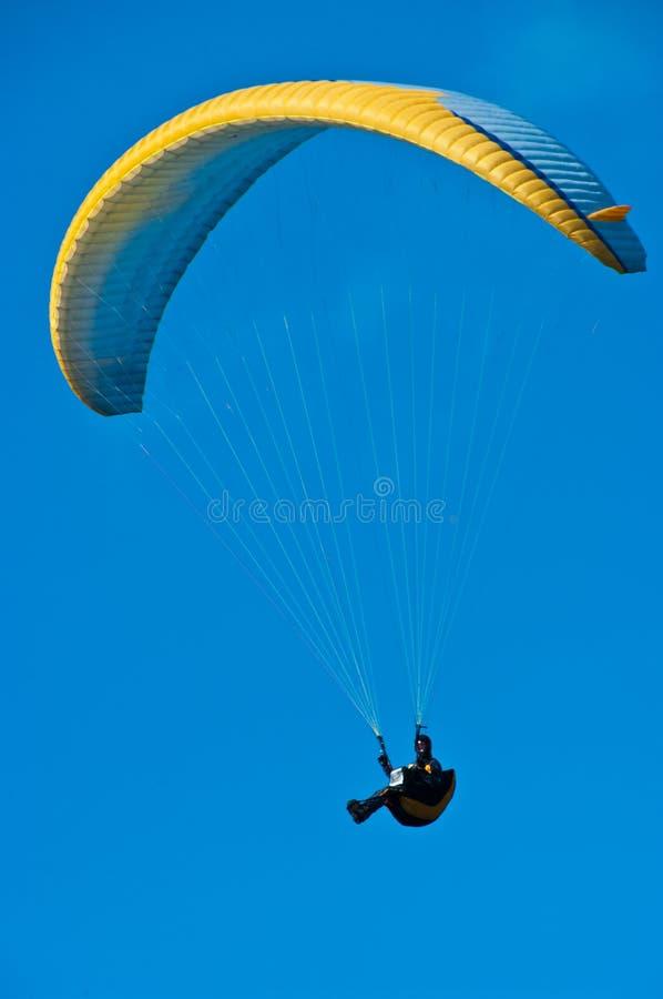 Gelber Fallschirm im blauen Himmel lizenzfreie stockfotografie