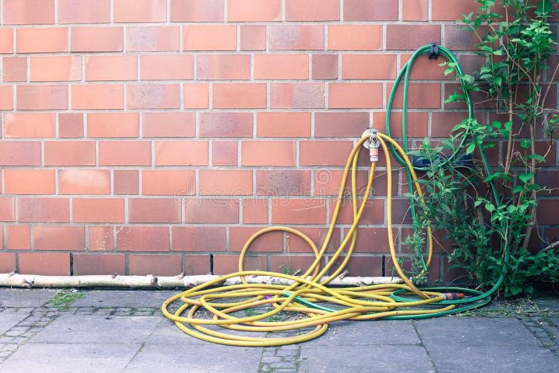 Gelber Gartenschlauch wickelte auf einem Haus ein lizenzfreies stockfoto