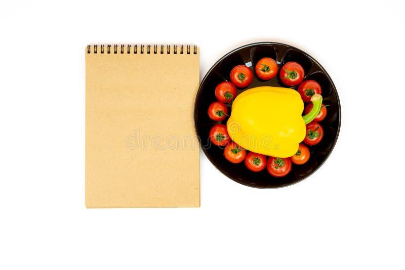 Gelber Gem?sepaprika mit Tomaten in einem Schwarzblech lokalisiert auf wei?em Hintergrund nahe Notizblock Zusammensetzung von gel stockfotos