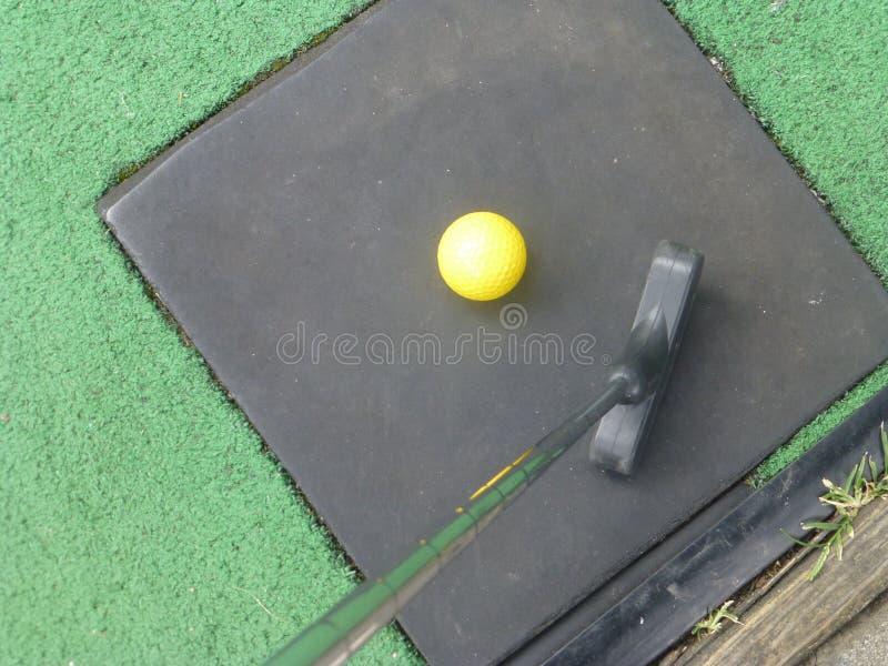 Gelber Golfball mit Putter stockfotos