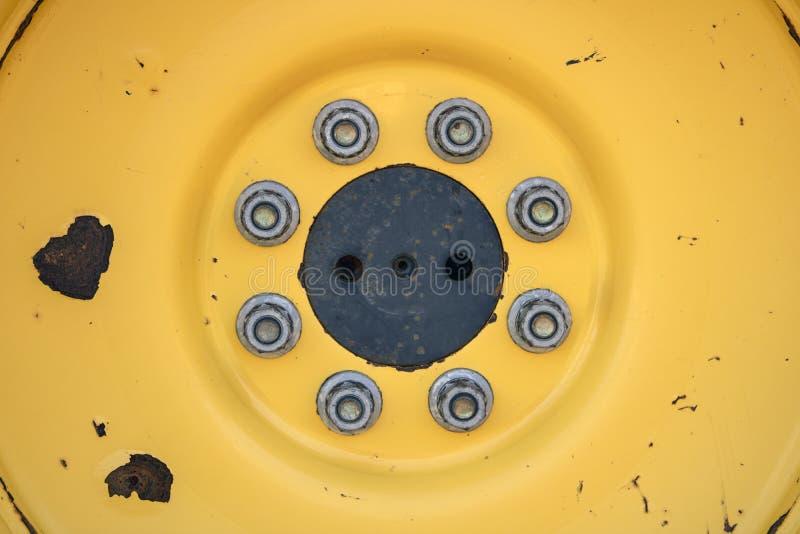 Gelber Hintergrund Nahaufnahmefoto eines gelben Traktorrades mit Nüssen - und - Bolzen Makro lizenzfreies stockfoto
