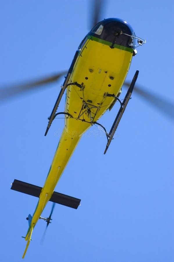 Gelber Hubschrauber im blauen Himmel lizenzfreie stockfotos