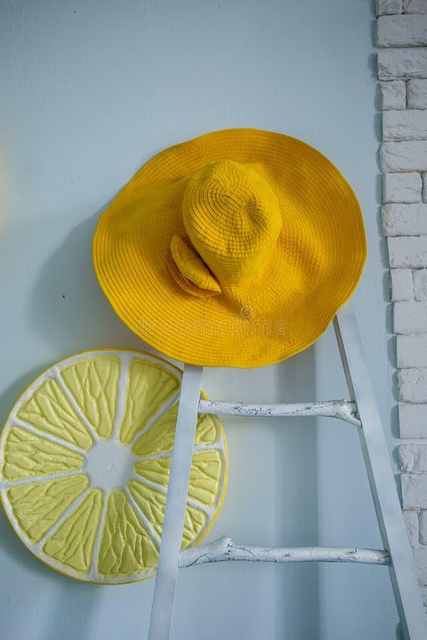 Gelber Hut und gelbe Zitrone in der Küche lizenzfreie stockfotos