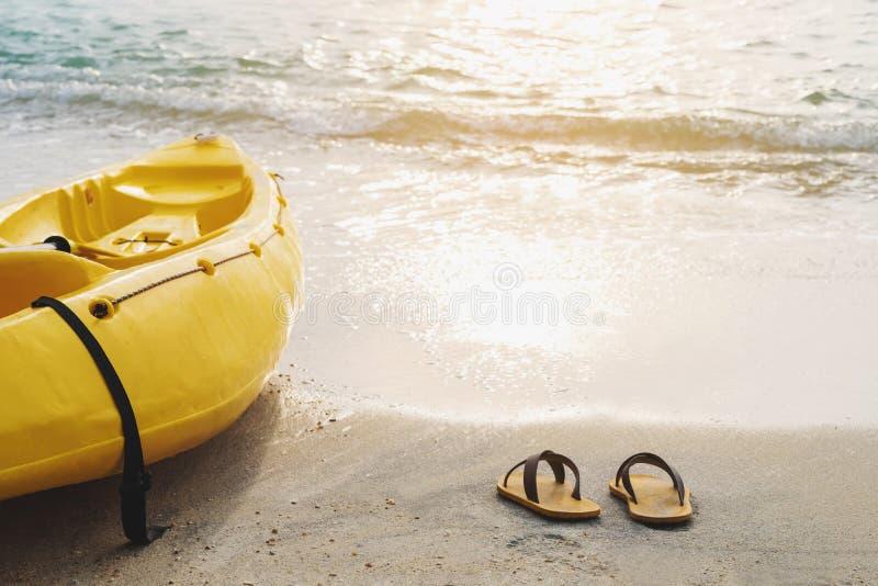 Gelber Kajak und Flipflop auf dem Strand im Sonnenuntergang, Sommerzeit-Ferienfeiertagskonzepte, Weinlesetonweichzeichnung lizenzfreies stockbild