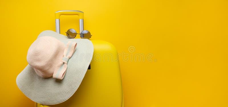 Gelber Koffer der Fahne, mit einem Hut für Erholung, den Strand und Sonnenbrille Reise-Sachen-Konzept-festliche Abenteuerreisen,  lizenzfreie stockbilder