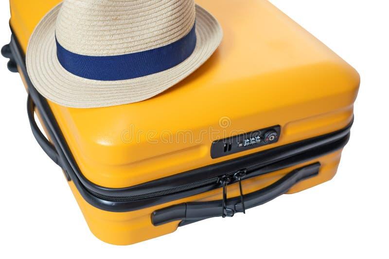 gelber Koffer mit einem Kombinationsschloß mit Nr. 666 auf ihm Sommerzeit - Reisetasche und -strohhut auf die Oberseite stockfoto