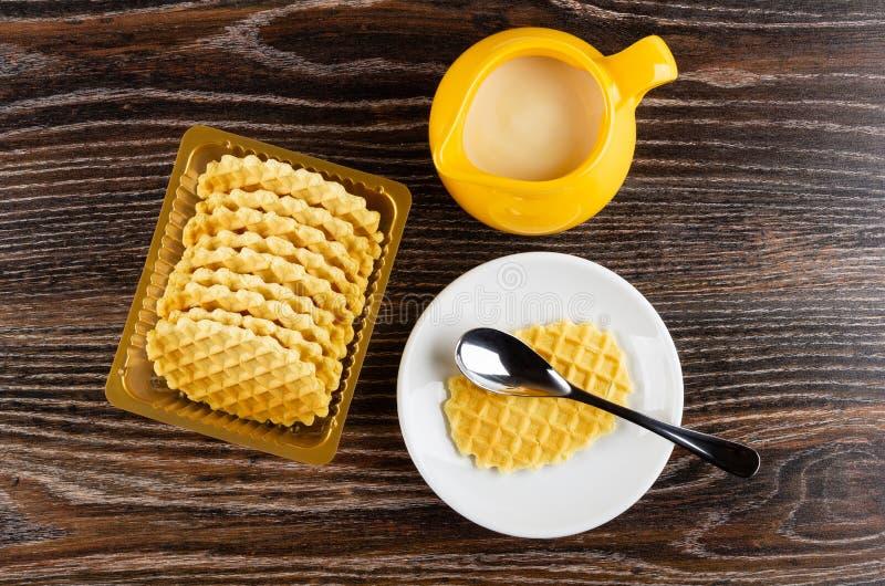 Gelber Krug mit Kondensmilch, Kasten mit Plätzchen, Plätzchen und Löffel in der Untertasse auf Holztisch Beschneidungspfad einges lizenzfreies stockfoto