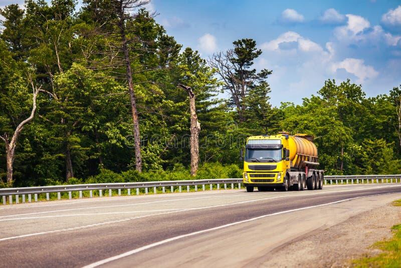 Gelber LKW mit Behältersattelschlepper auf einer Straße stockbilder