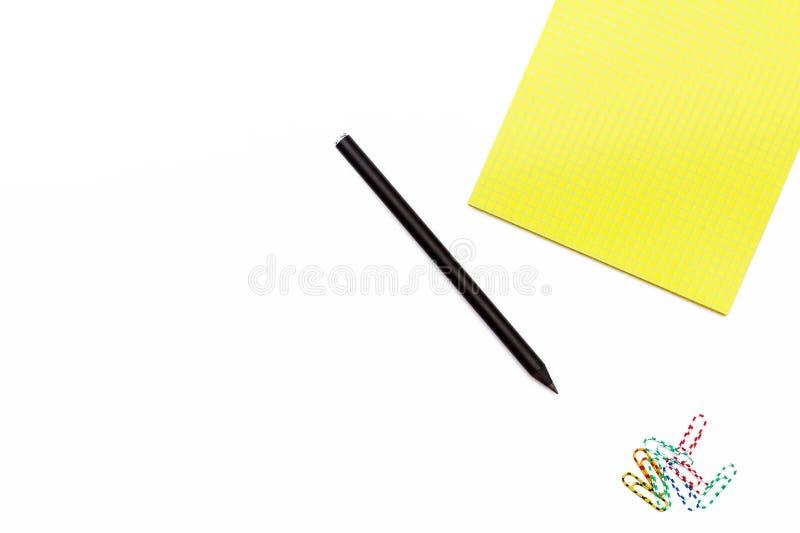 Gelber Notizblock und ein schwarzer Bleistift mit Büroklammern auf einem weißen Hintergrund Minimales Arbeitskonzept für Schreibt stockfotos