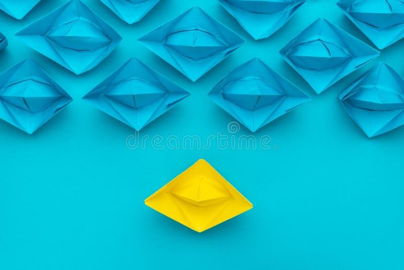 Gelber Papierschiffsstand aus dem Mengenkonzept über blauem Hintergrund heraus stockfoto