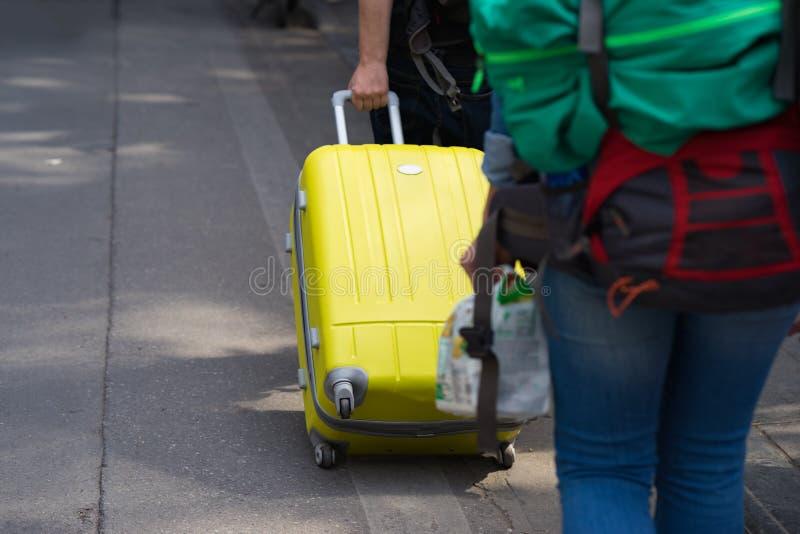 Gelber Reisekoffer zog durch Mannhand auf Straße Konzept der Reise stockfoto