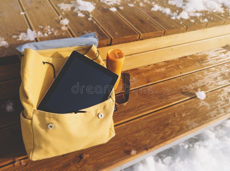 Gelber Rucksack, Thermosflasche mit heißem Getränk und Hippie-Gerättablette mit einem sauberen leeren Bildschirm auf einem Hinter lizenzfreie stockfotos