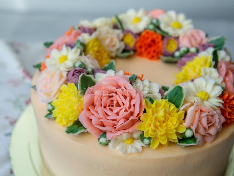 Gelber Sahnekuchen verziert mit buttercream Blumen - Pfingstrosen, Rosen, Chrysanthemen, Gartennelken - auf weißem hölzernem Hint stockfotografie