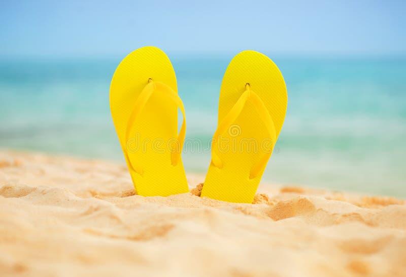 Gelber SandaleFlipflop auf dem weißen Sandstrand mit blauem See- und Himmelhintergrund in Sommerferien kopieren Raum stockbilder