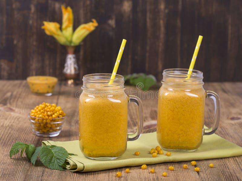 Gelber Sanddornsaft in einem Glas und reifen in einem Yellow- Seawegdorn auf einem Weinleseholztisch Gesundes BioLebensmittel und stockfoto