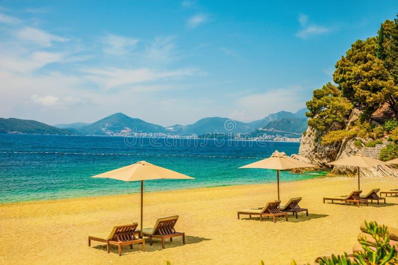 Gelber sandiger Strand mit Sonnenruhesesseln an einem sonnigen Tag Bergspitzen sichtbar im Abstand Schöner Seehintergrund lizenzfreies stockbild