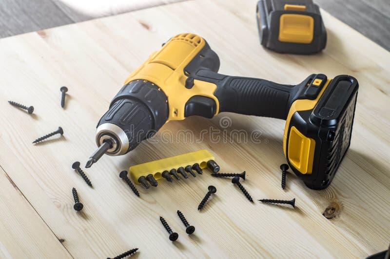 gelber Schraubenzieher auf einem Holztisch, Schrauben, ein Satz Stückchen stockfoto