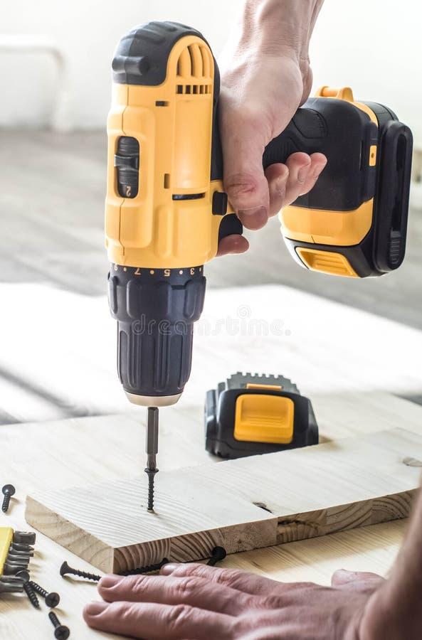gelber Schraubenzieher auf einem Holztisch, Schrauben, ein Satz Stückchen lizenzfreie stockfotos