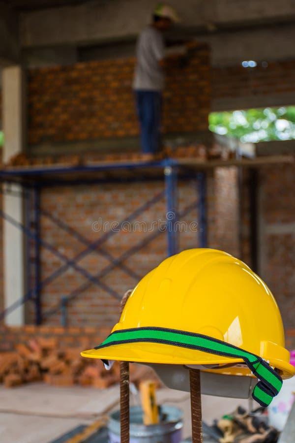 Gelber Schutzhelm mit dem Bauarbeiter, der an Ziegelsteine setzt lizenzfreies stockbild