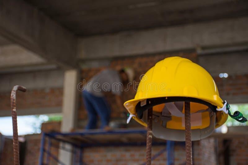 Gelber Schutzhelm mit dem Bauarbeiter, der an Ziegelsteine setzt stockfotos