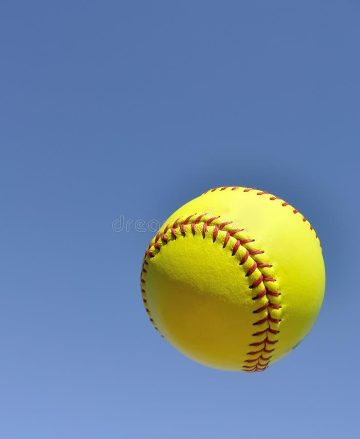 Gelber Softball in der Luft lizenzfreie stockfotos