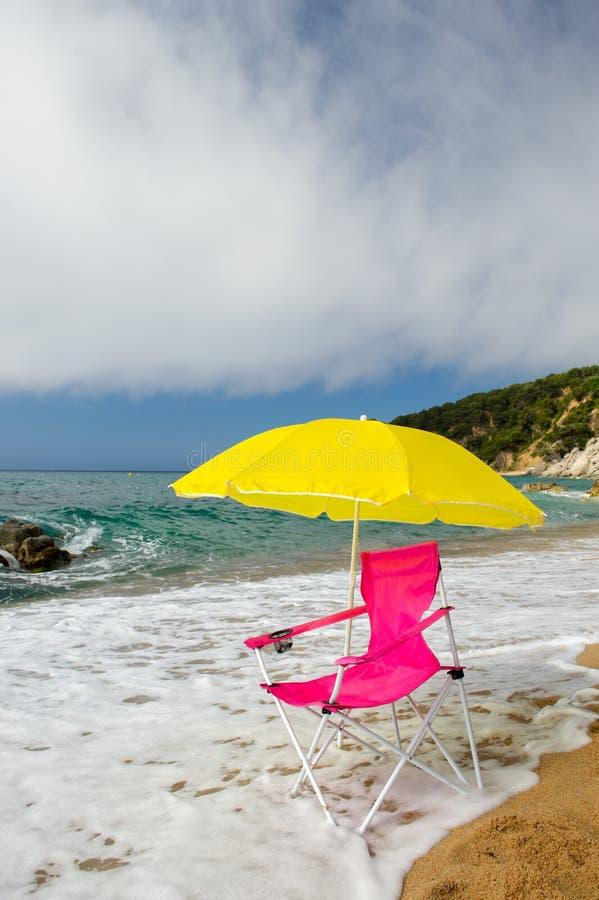 Gelber Sonnenschirm und rosa Stuhl am Strand stockfotografie