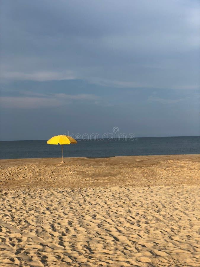 Gelber Strandschirm gegen einen verärgerten Himmel lizenzfreie stockfotografie