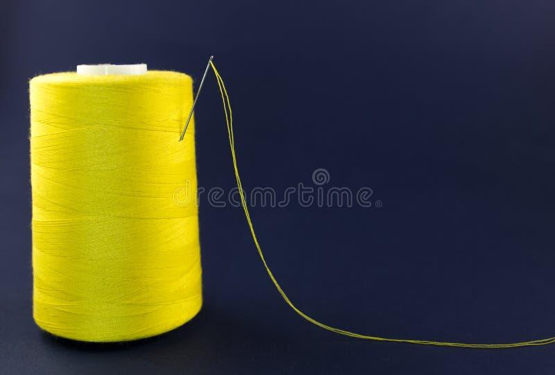 Gelber Strang des Threads mit einer Nadel auf einem blauen Hintergrundgelb lizenzfreies stockbild