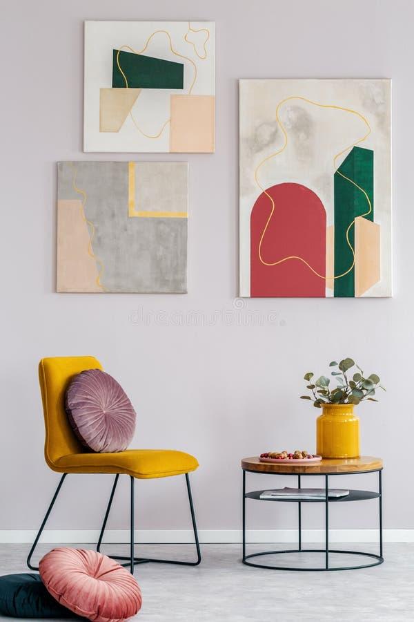 Gelber Stuhl mit rundem Kissen nahe bei hölzernem Couchtisch mit Blumen im Vase stockbild