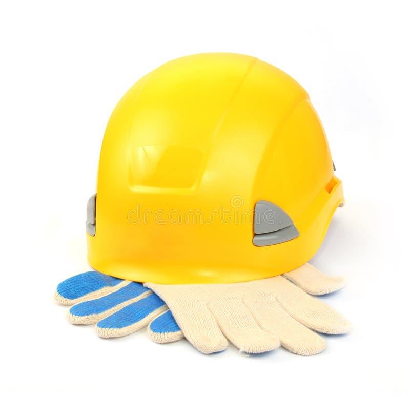 Gelber Sturzhelm und Arbeitshandschuhe stockfotos