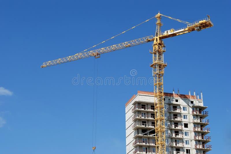 Gelber Turmkran am mehrstöckigen Gebäude stockfotos