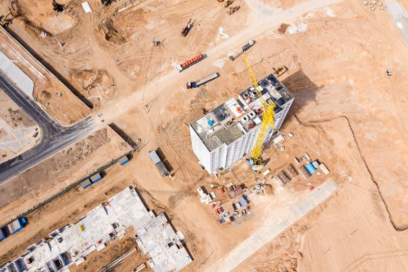 Gelber Turmkran und andere Maschinerie, die an der StadtBaustelle arbeitet Brummenphotographie stockfotos
