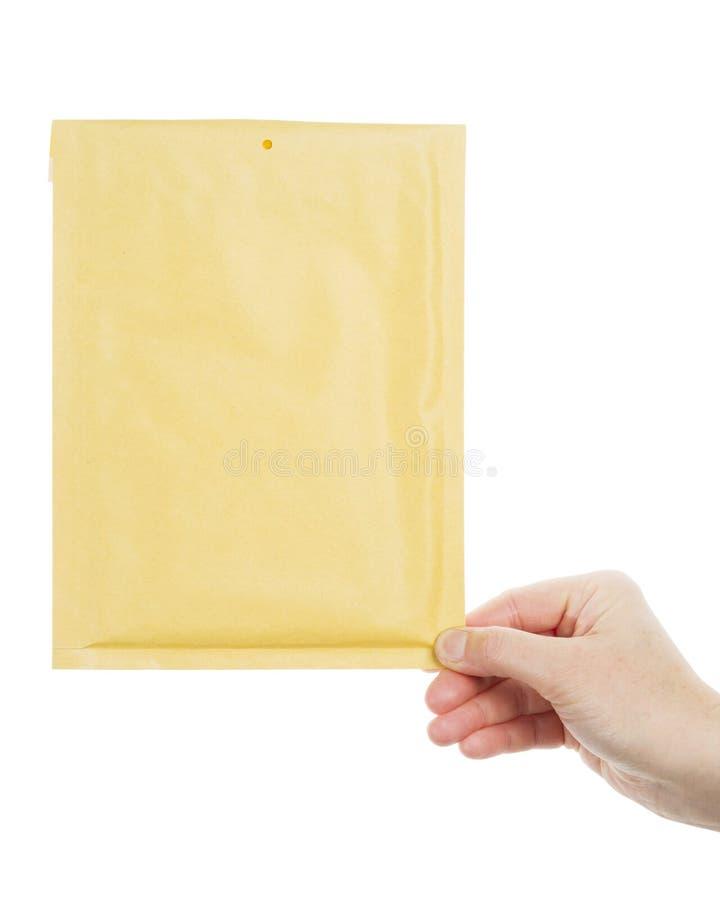 Gelber Umschlag in der Hand stockbild
