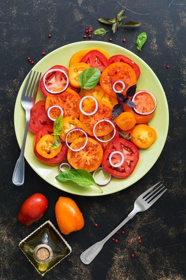 Gelber und roter frischer Tomatensalat mit Basilikum und Zwiebel auf einem dunklen rustikalen Hintergrund Flache Lage, Draufsicht lizenzfreies stockfoto