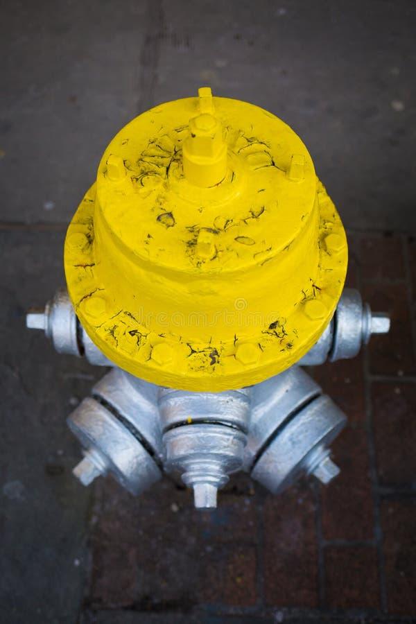 Gelber und silberner Hydrant auf der Straße lizenzfreie stockbilder