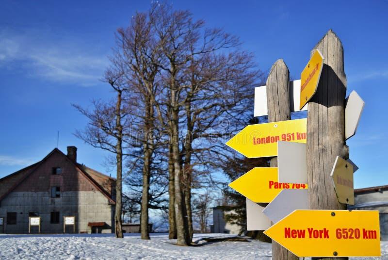 Gelber Wegweiser zu den großen Weltstädten im Winterland stockfotos