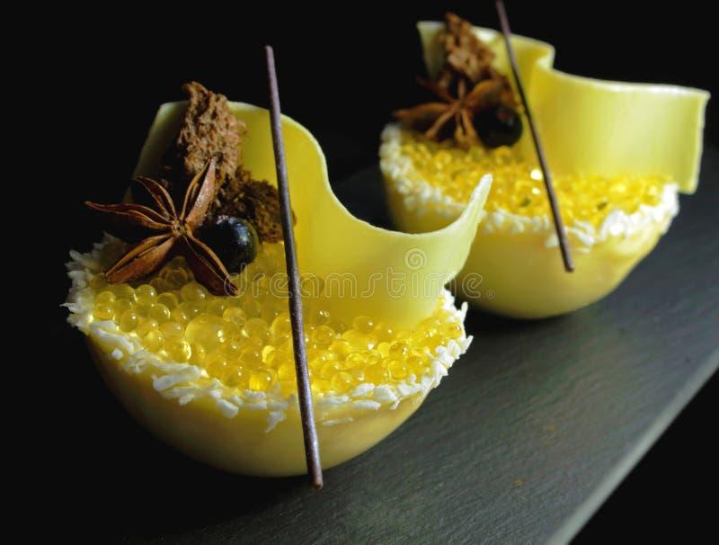 Gelber Zitronengeleeunterwasserkaviar und weißer Melonenkremeisnachtisch mit Kokosnuss, Honig, weißer Schokolade und Sternanis stockbild