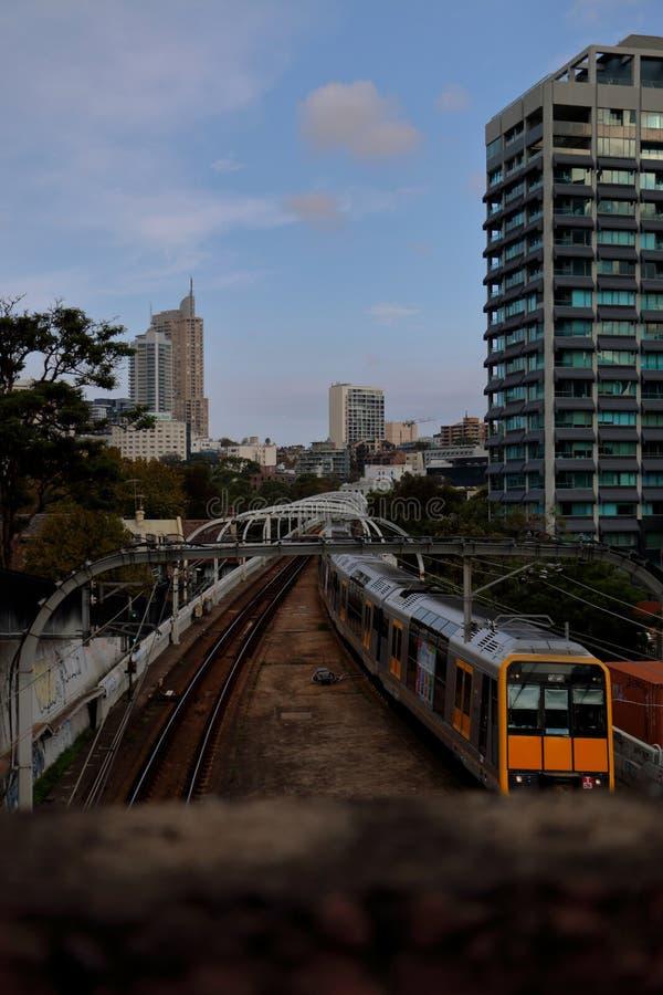 Gelber Zug, der zur Stadt mit blauem Himmel zurückkommt stockfotografie