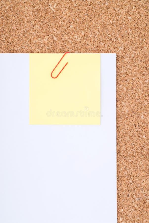 Gelbes Anmerkungs-Papier mit Papierklammer auf Weißbuch ov lizenzfreie stockfotos