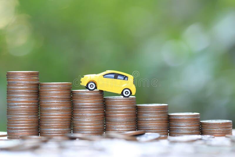 Gelbes Autominiaturmodell auf wachsendem Stapel des Münzengeldes auf Naturgrünhintergrund, des Rettungsgeldes für Auto, der Finan stockfotografie