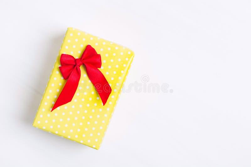 Gelbes beschmutztes Geschenk mit rotem Bogen über weißem strukturiertem Hintergrund, alles Gute zum Geburtstag, Feriengeschenk lizenzfreies stockbild