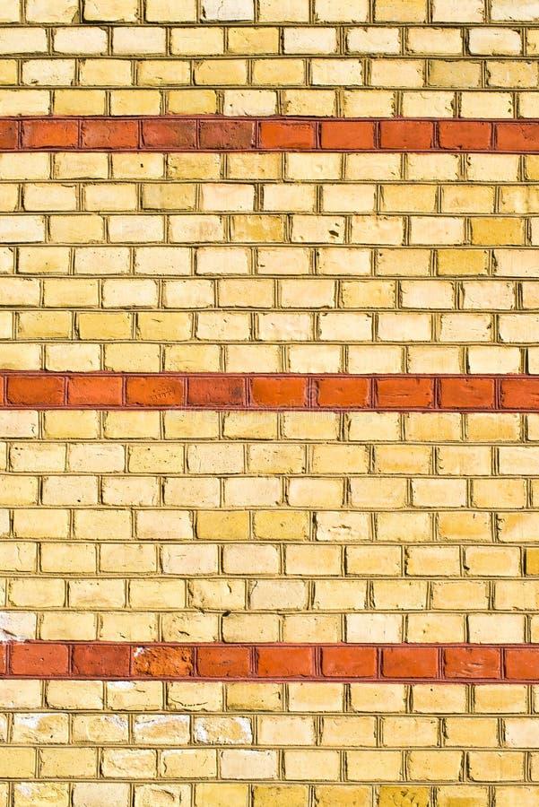 Gelbes brickwall mit roten Streifen stockfotografie