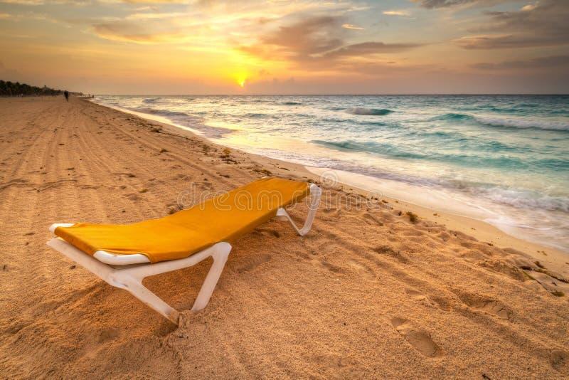 Gelbes deckchair am karibischen Sonnenaufgang stockbild