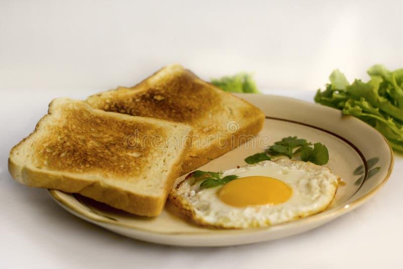 Gelbes Eigelb des Spiegeleies des Gesundheitsfrühstücks, Toastbrot, Wurst, Gemüse am Morgen lizenzfreie stockbilder
