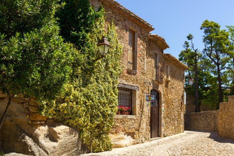Gelbes entsteintes Haus und Straße in der Sonne in Catelonia stockfoto