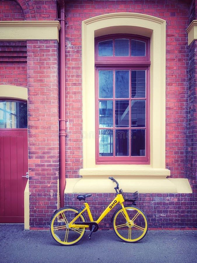 Gelbes Fahrrad und Backsteinbau stockbilder
