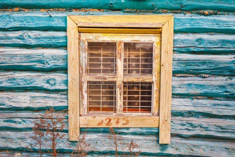 Gelbes Fenster im alten Türkisholzhaus stockfotografie