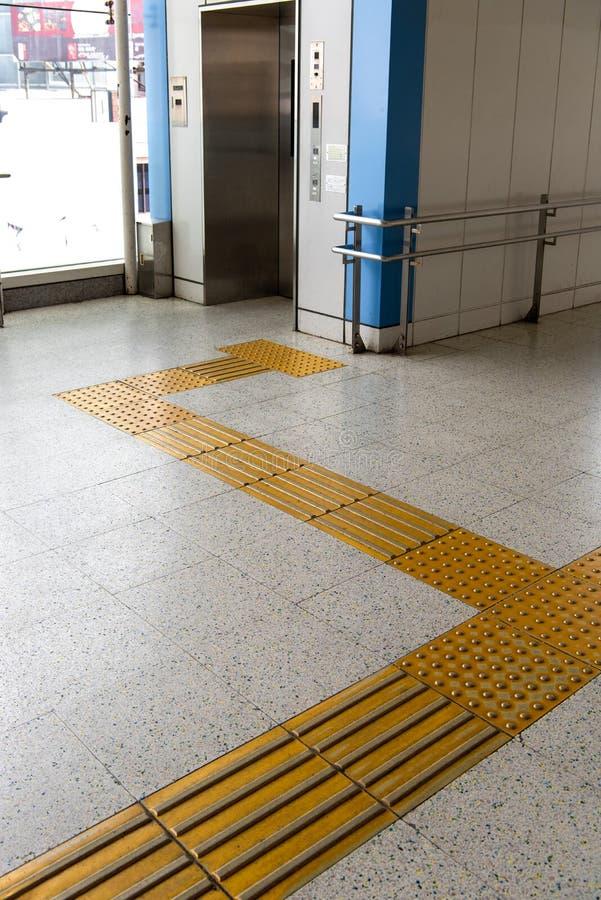 Gelbes Gehen für die Person mit Sehstörungen, Aufzug stockfotografie