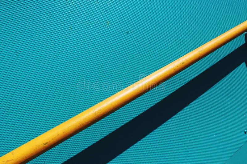 Gelbes Geländer mit blauer Türkishintergrundwand stockfoto